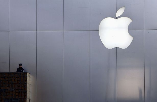 A-policeman-looks-out-from-a-balcony-as-the-crowd-is-dispersed-from-the-front-of-an-Apple-store-in-Beijing.-AP-Photo