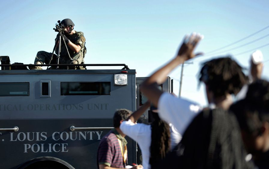 A member of the St. Louis County Police Department points his weapon in the direction of a group of protesters in Ferguson, MO.