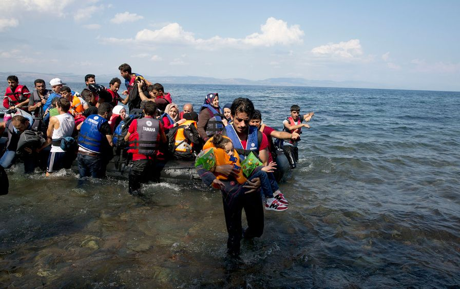 A man carries a child as migrants and refugees arrive on a dinghy after crossing from Turkey to Lesbos island, Greece.