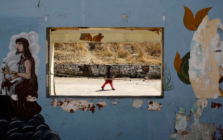A girl walks at a refugee and migrant camp on the northeastern Greek island of Lesvos.