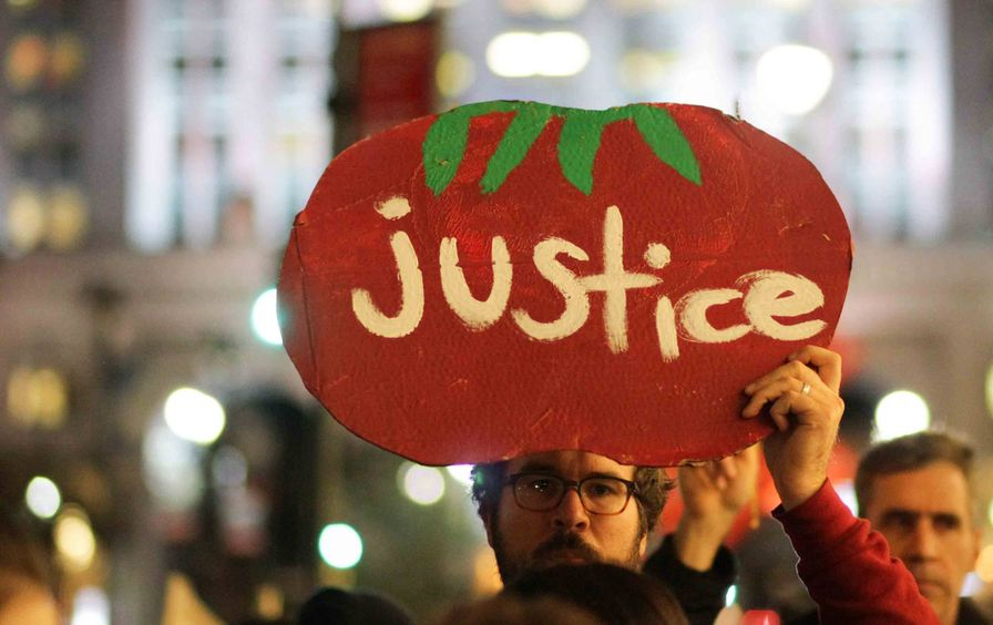 A marcher holds a sign at the Coalition of Immokalee Workers's rally for just working conditions in Florida tomato fields, November 16, 2015.
