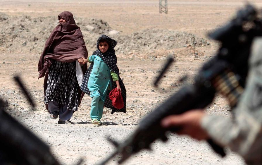 An Afghan woman and girl approach American troops in Kandahar.