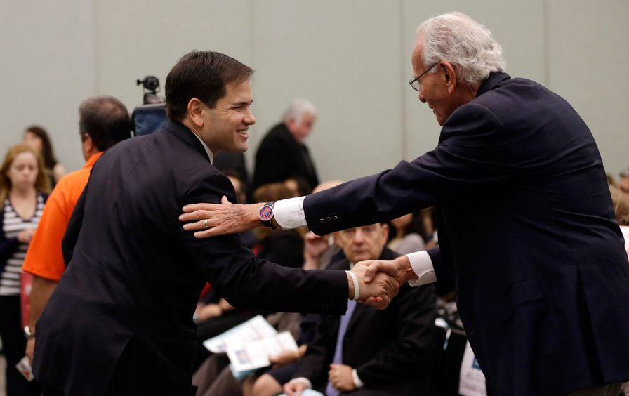 Marco Rubio shakes hands with major donor and former employer Norman Braman in Miami.