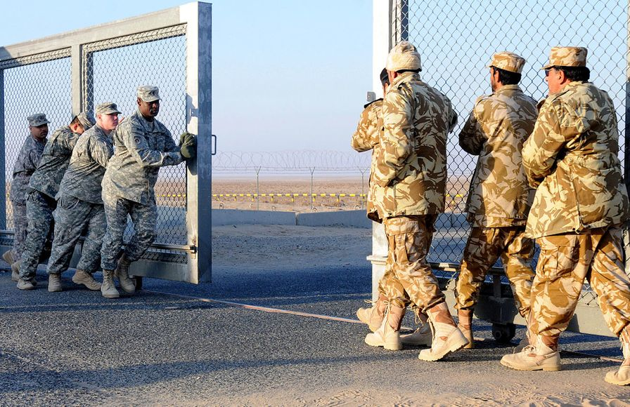 US and Kuwaiti soldiers close a gate between Iraq and Kuwait in December 2011.