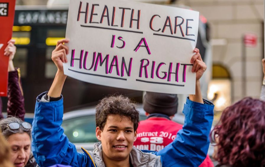 A young man holds up a sign at a recent rally against the repeal of the ACA