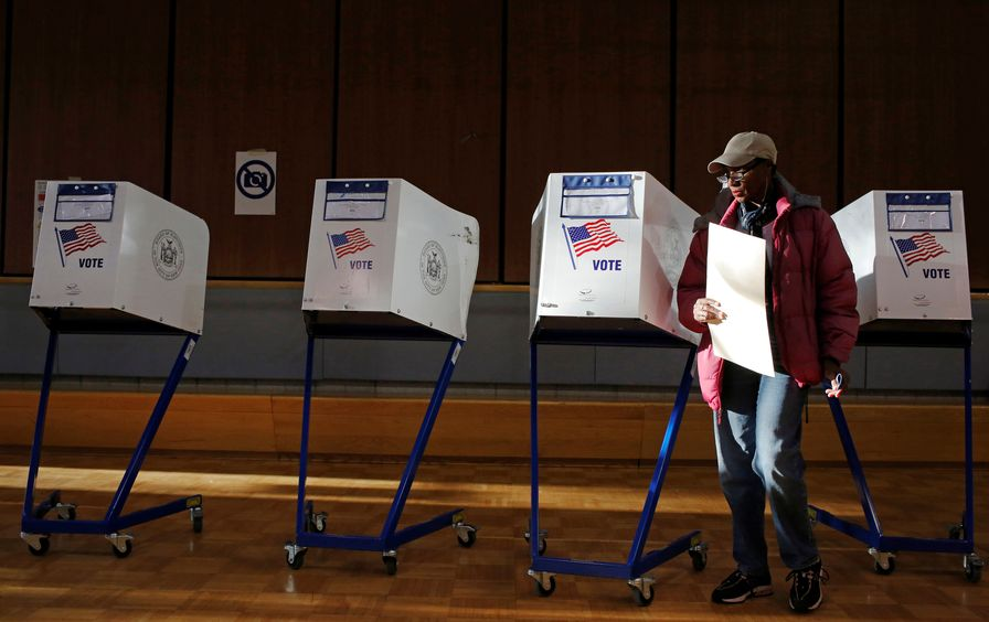 A woman exits the voting booth after filling out her ballot for the U.S presidential election at the James Weldon Johnson Community Center in the East Harlem neighbourhood of Manhattan, New York City