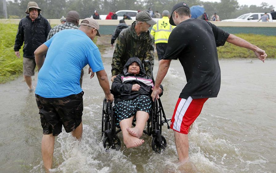 An elderly woman in a wheelchair is rescued from the flood waters of tropical storm Harvey in east Houston, Texas, U.S., August 28, 2017.