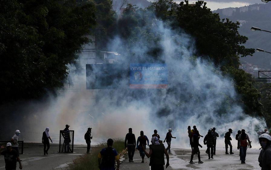 Demonstrators walk amid tear gas fired by Bolivarian National Guards on the outskirts of Caracas, Venezuela on July 20, 2017.