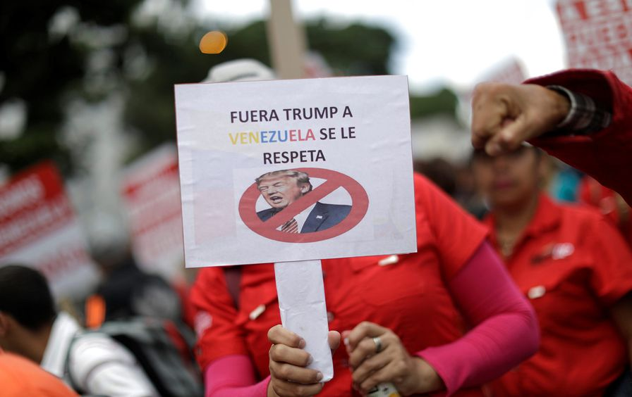 A pro-government supporter holds a sign that reads