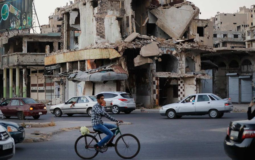 A man rides his bike past damaged buildings in the old town of Homs, Syria, on August 15, 2018.