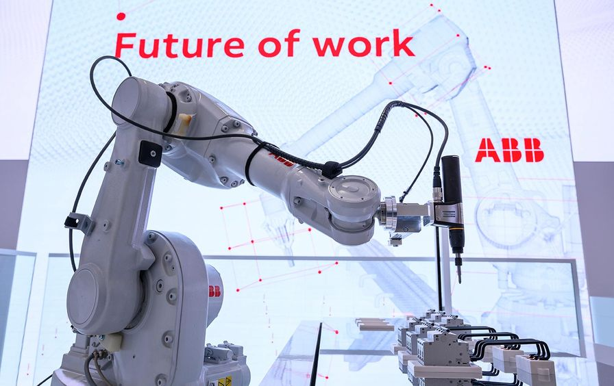 A booth at the 2019 Hannover Messe industrial technology trade fair in Lower Saxony, Hannover, on March 31 shows a robot with a white arm. The robot art is against a white background with the words