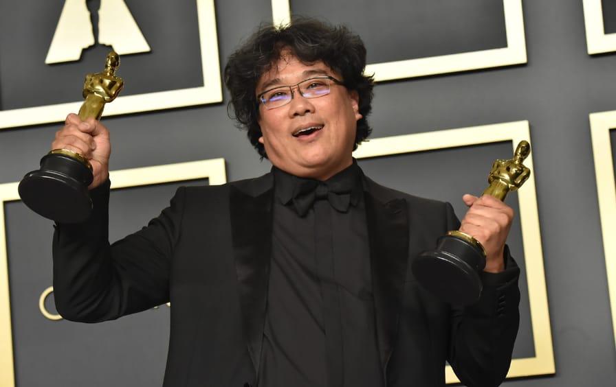 Bong Joon-ho holding two Oscars.