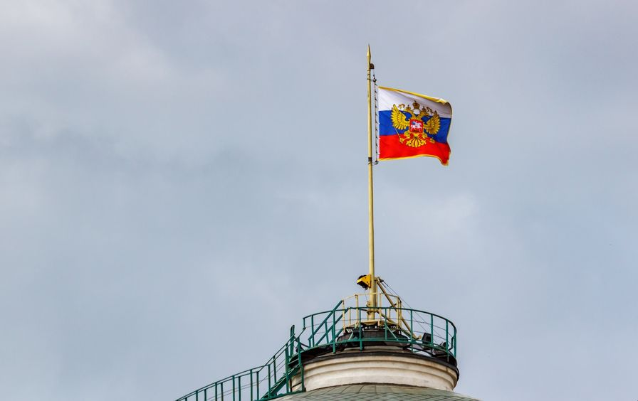 Flag of Russian Federation with gilded coat of arms waving on the dome of Senate Palace of Moscow Kremlin