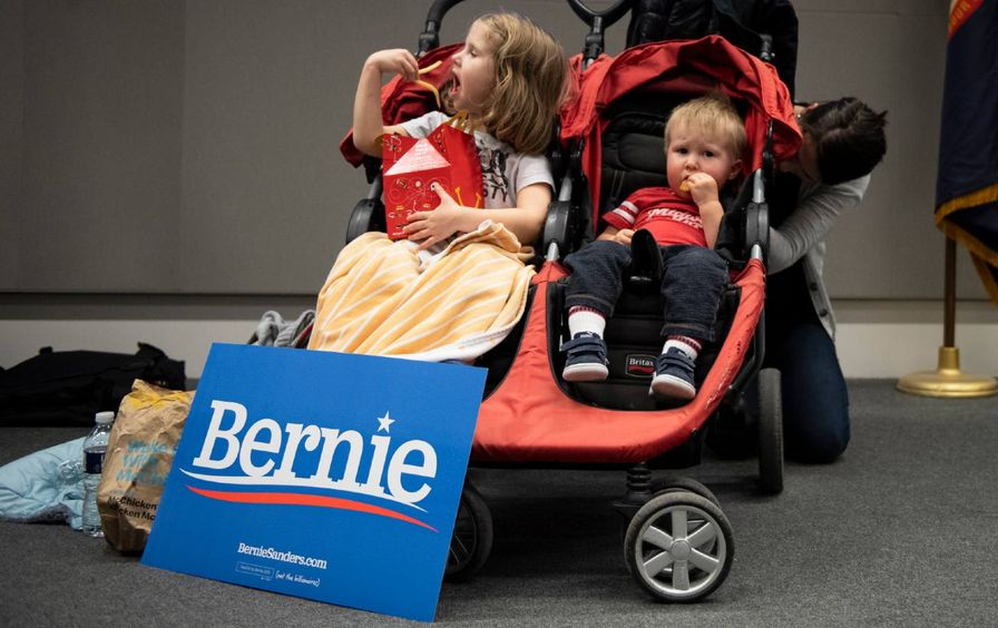 two children eat in their stroller at a satellite caucus