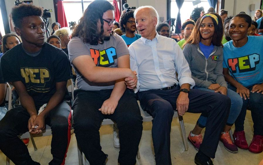 Biden shaking hands with a young voter
