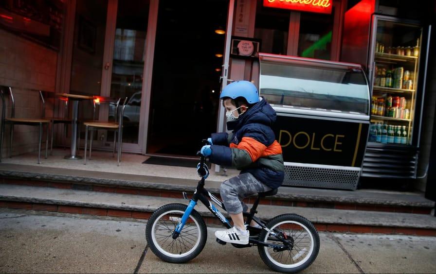 A boy rides his bike through Boston with a mask