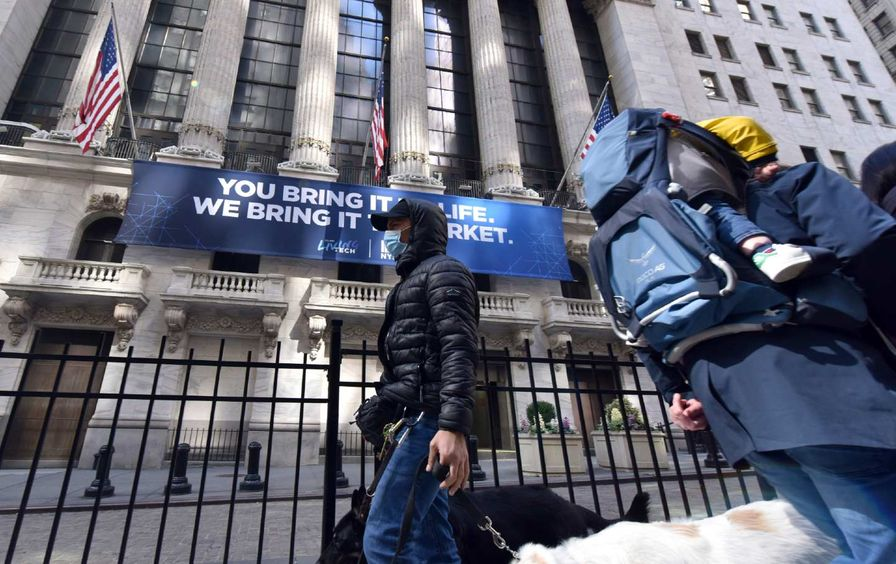 A man wearing a protective mask and passing in front of the New York Stock Exchange, walking his dog.