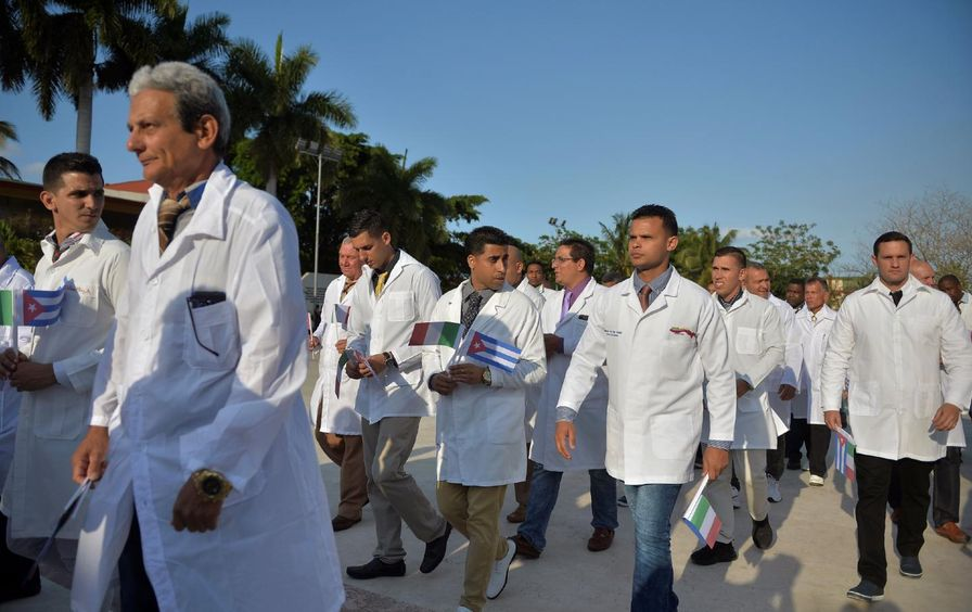 A group of doctors and nurses walk outside, holding small Cuban and Italian flags.