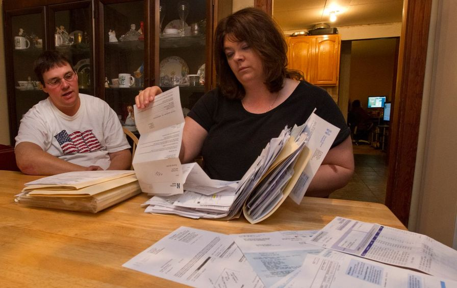 Glenn and Tracy McCarthy in their home with a pile of medical bills