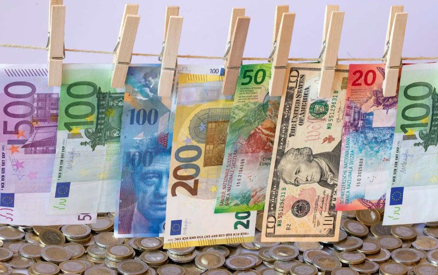EURO, Swiss Franc and Dollar banknotes on a washing line and coins