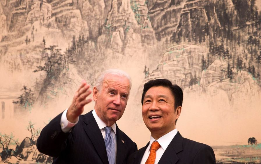 Joe Biden gestures while speaking with a smiling Li Yuanchao