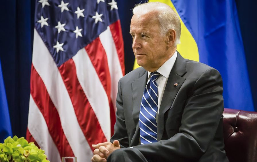 Biden sits in front of a US flag