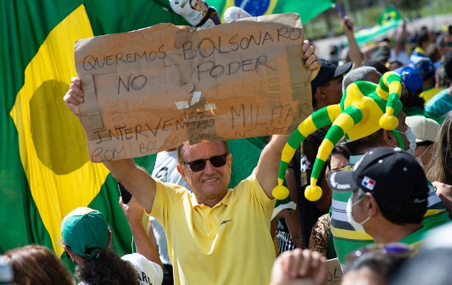 A man with sunglasses holds a cardboard sign, with writing in Portuguese.