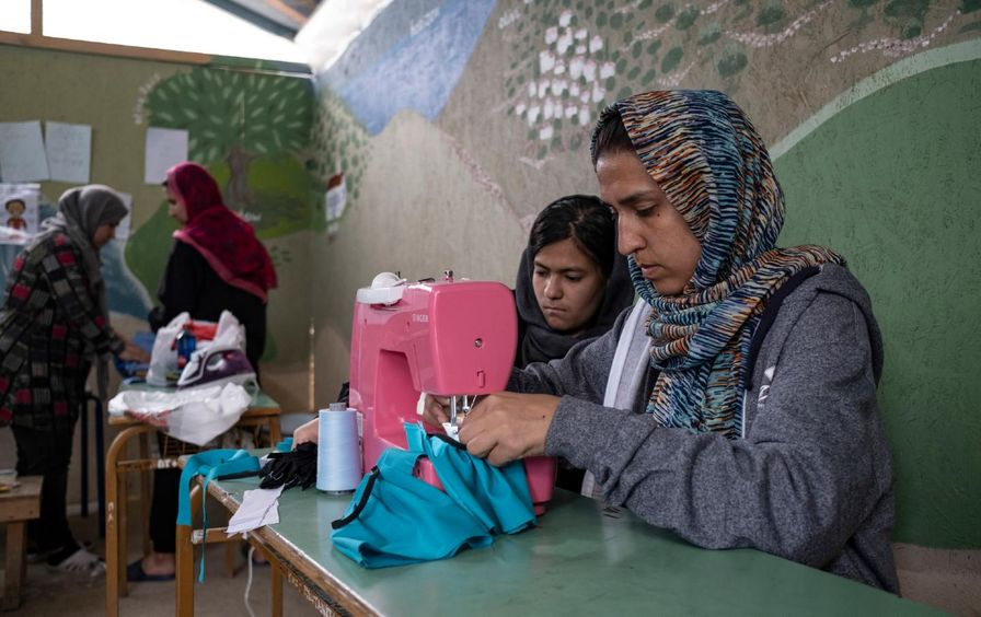 Two women focus on a sewing machine.