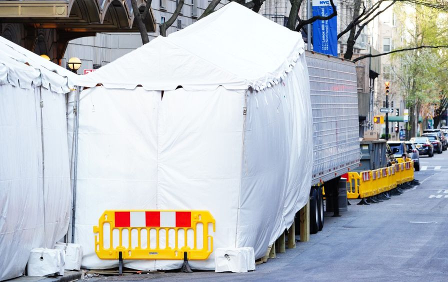 A trailer attached to a tent sits on the street near a hospital