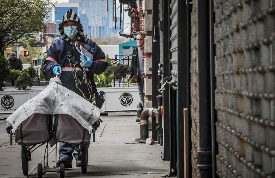 A postal worker delivers mail in Harlem with a mask
