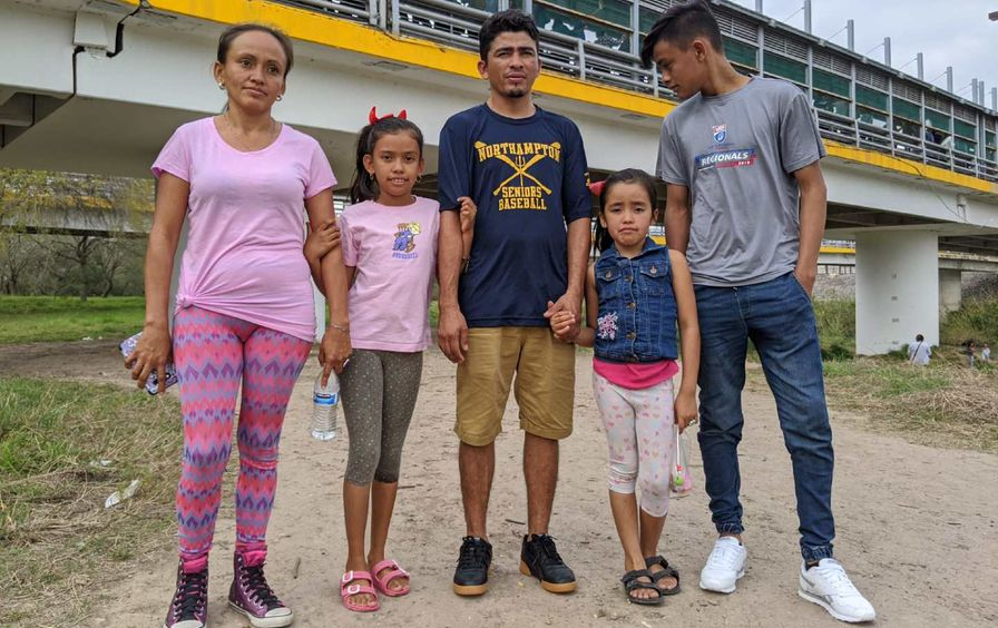 Family of 5 pose for a photograph.