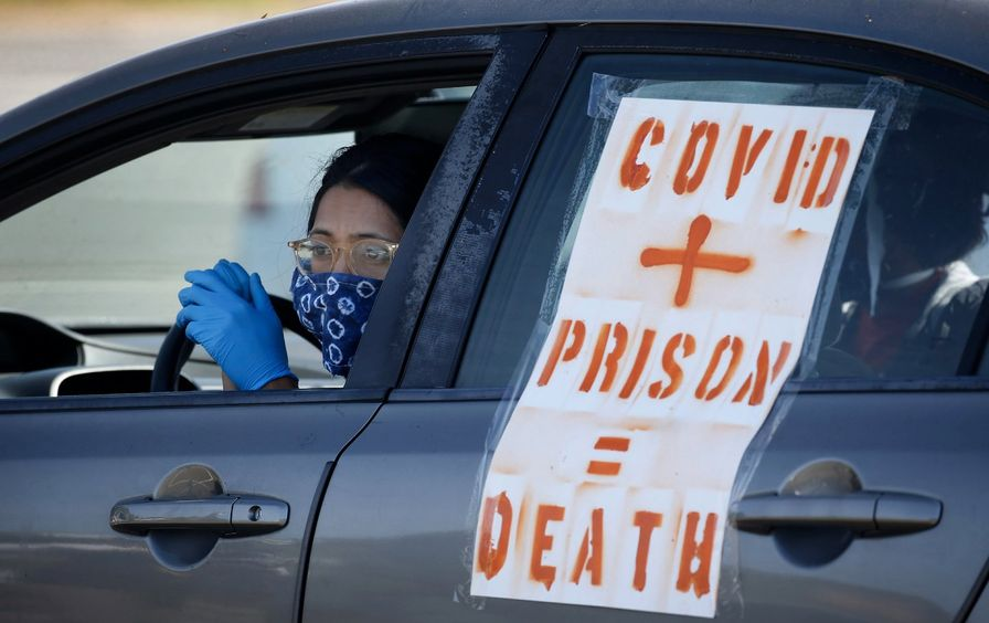 A women in a car with a poster reading