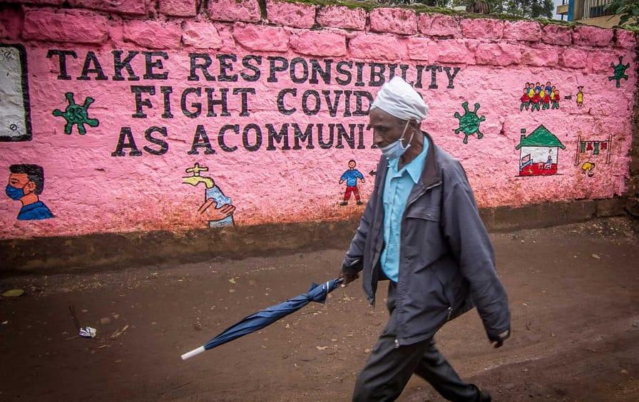 A man walking with a face mask in Kibera, a slum of Nairobi