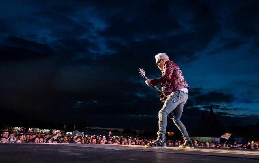 Rudolf Schenker plays guitar on stage to a large crowd