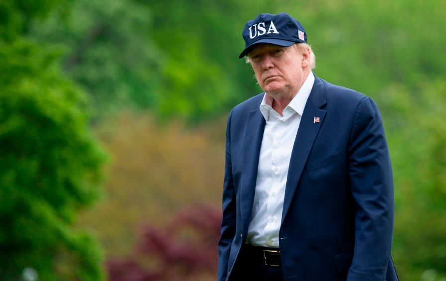 Donald Trump walks while outside, wearing a blue suit and blue hat that says