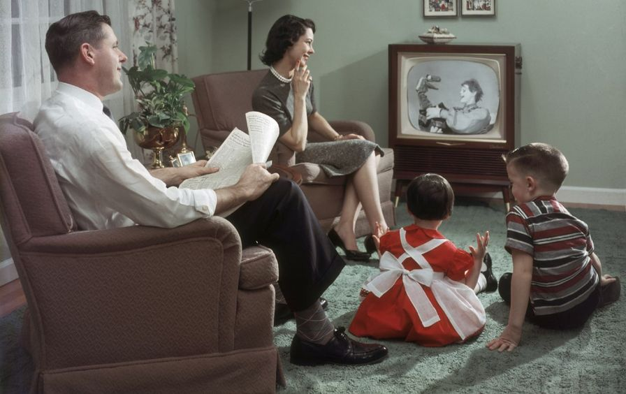 A man, a woman and two children sit around a television.