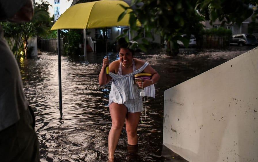 Woman with yellow umbrella walking through Miami