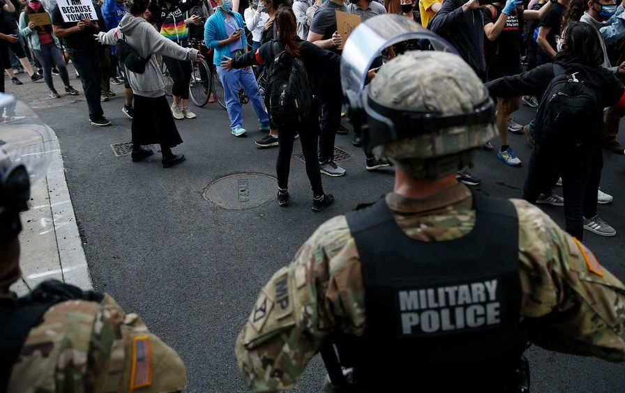 Military police face crowd of marching protesters