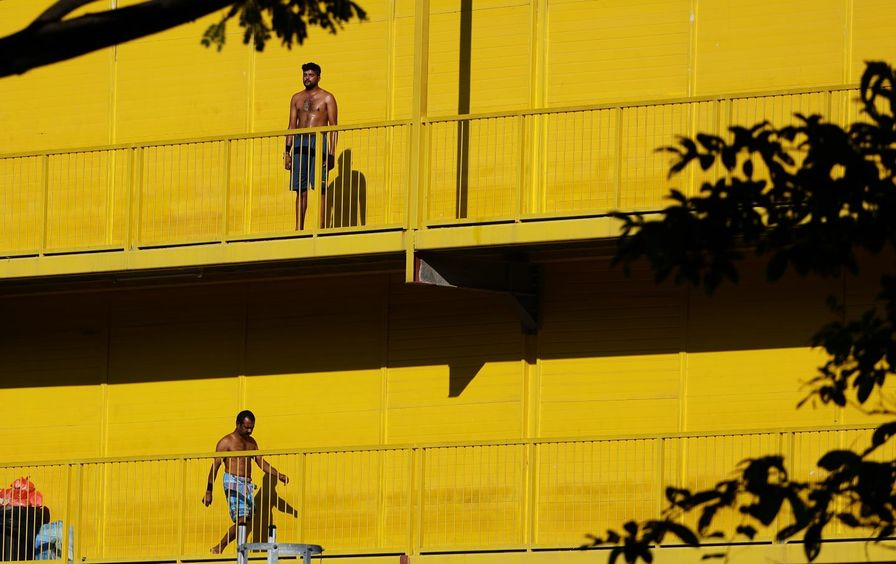 Men exercising without shirts against a yellow building in Singapore.