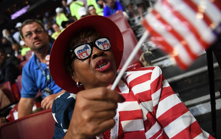 A delegate wearing Democratic Party sunglasses and an American flag suit waves an American flag.