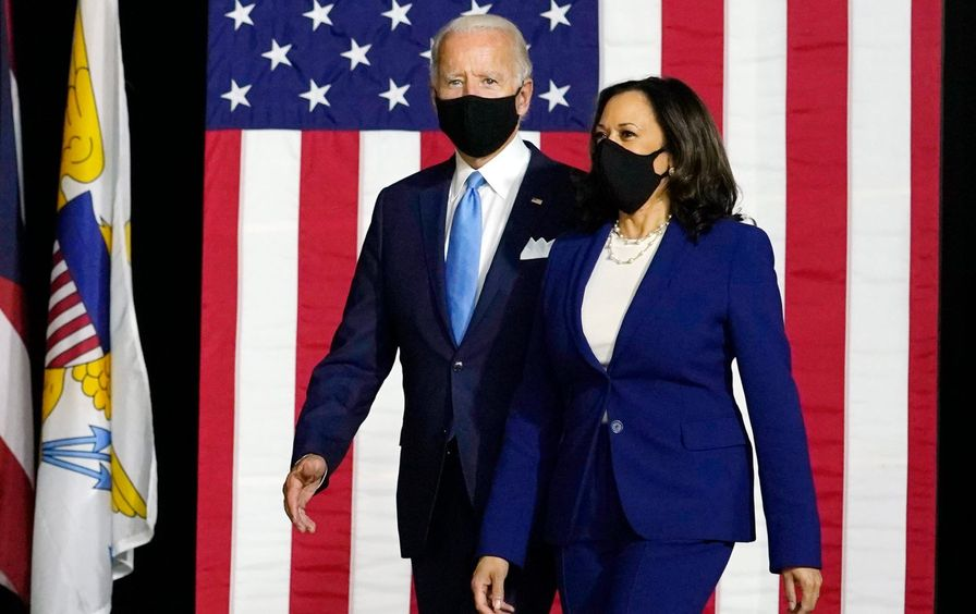 Biden and Kamala walking in front of an American flag