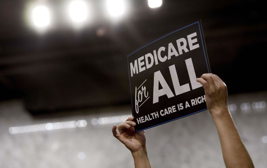 Someone holds up a Medicare for All sign at a rally for former candidate Bernie Sanders.