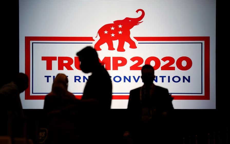 Silhouettes walk past a sign with the RNC logo and reads
