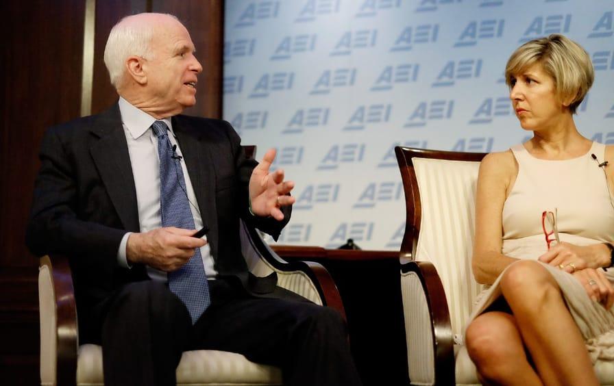 John McCain sits on stage talking to Danielle Pletka
