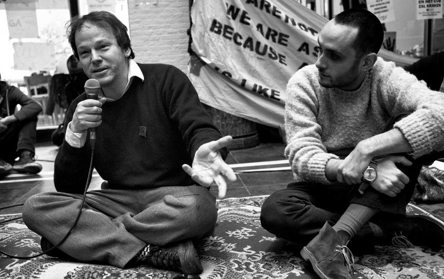 David Graeber holds a microphone and speaks at an occupation