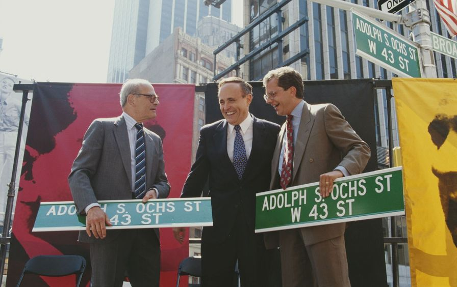 Two men hold street signs reading