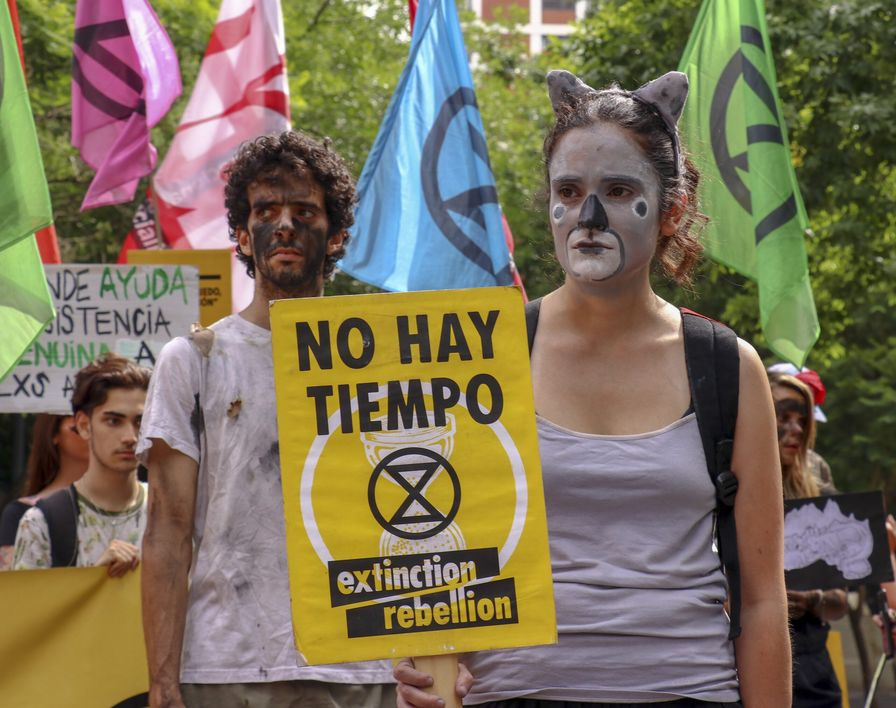 Two activists with painted faces stand, holding a sign that reads