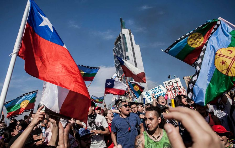 A crowd of protesters, several with Chilean flags