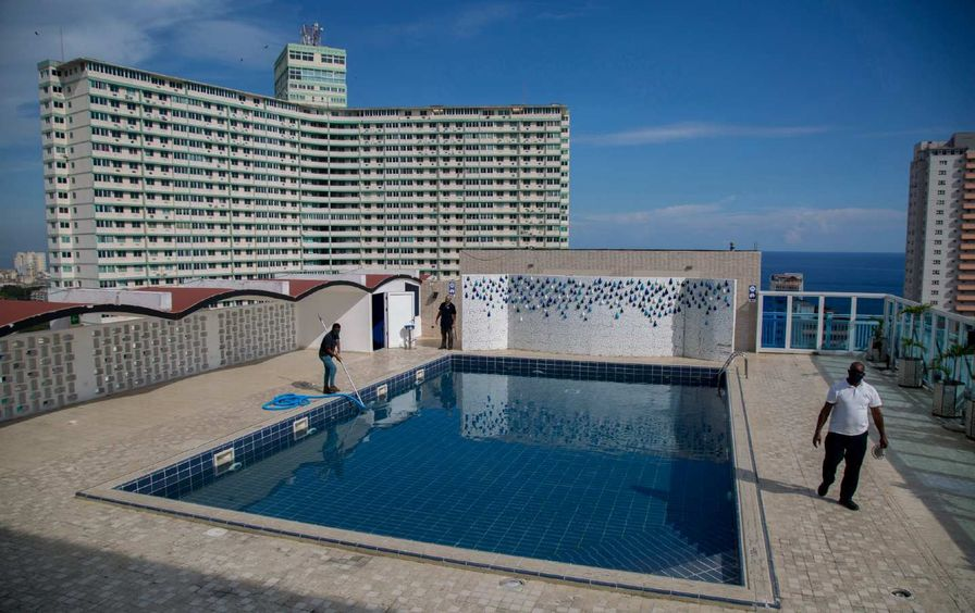Workers clean a rooftop pool while a large building is seen in the background.