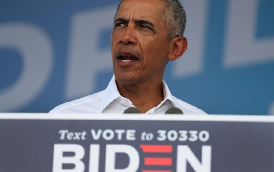 Barack Obama speaks to a crowd in front of a Biden 2020 sign